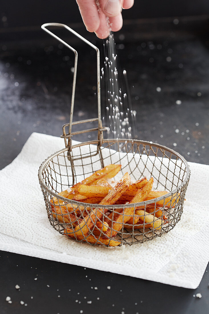 Chips in a frying basket being sprinkled with salt