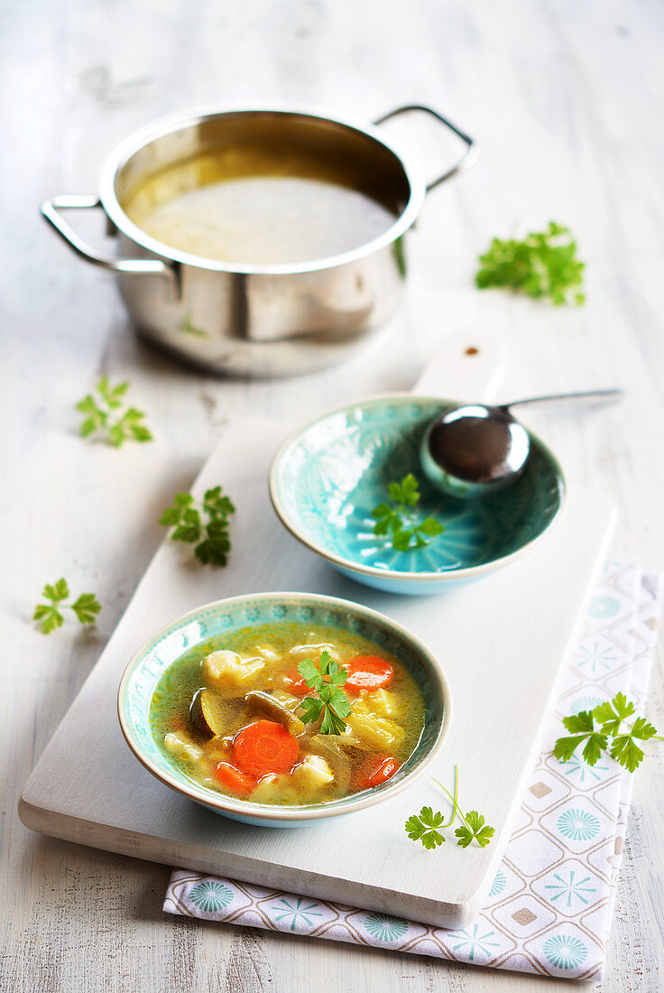 Vegetable soup in a small bowl on a board with a kitchen towel