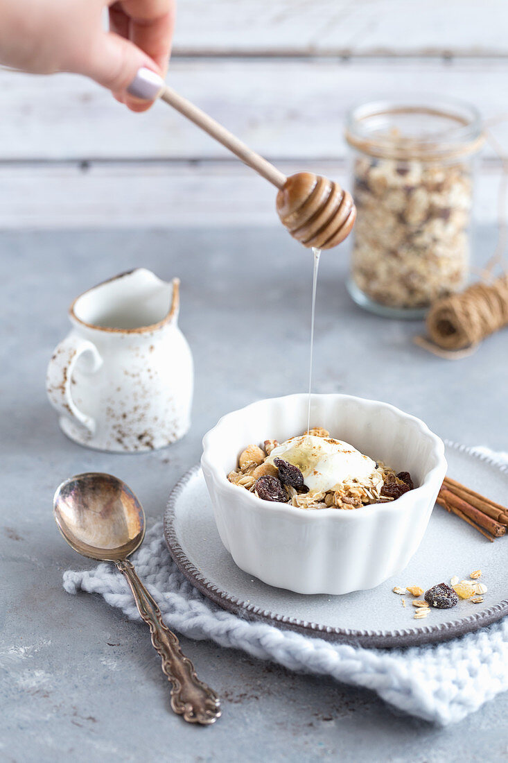 Granola and joghurt in a white bowl pouring honey on the top