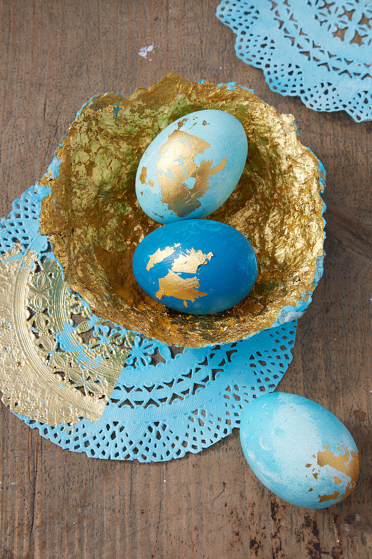 Easter eggs and handmade papier-mâché bowl decorated in blue and gold