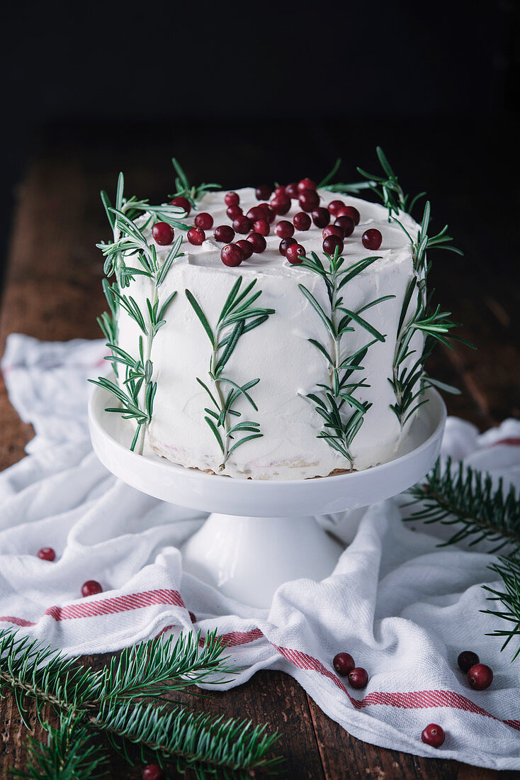 Christmas mascarpone cake decorated with rosemary and cranberries