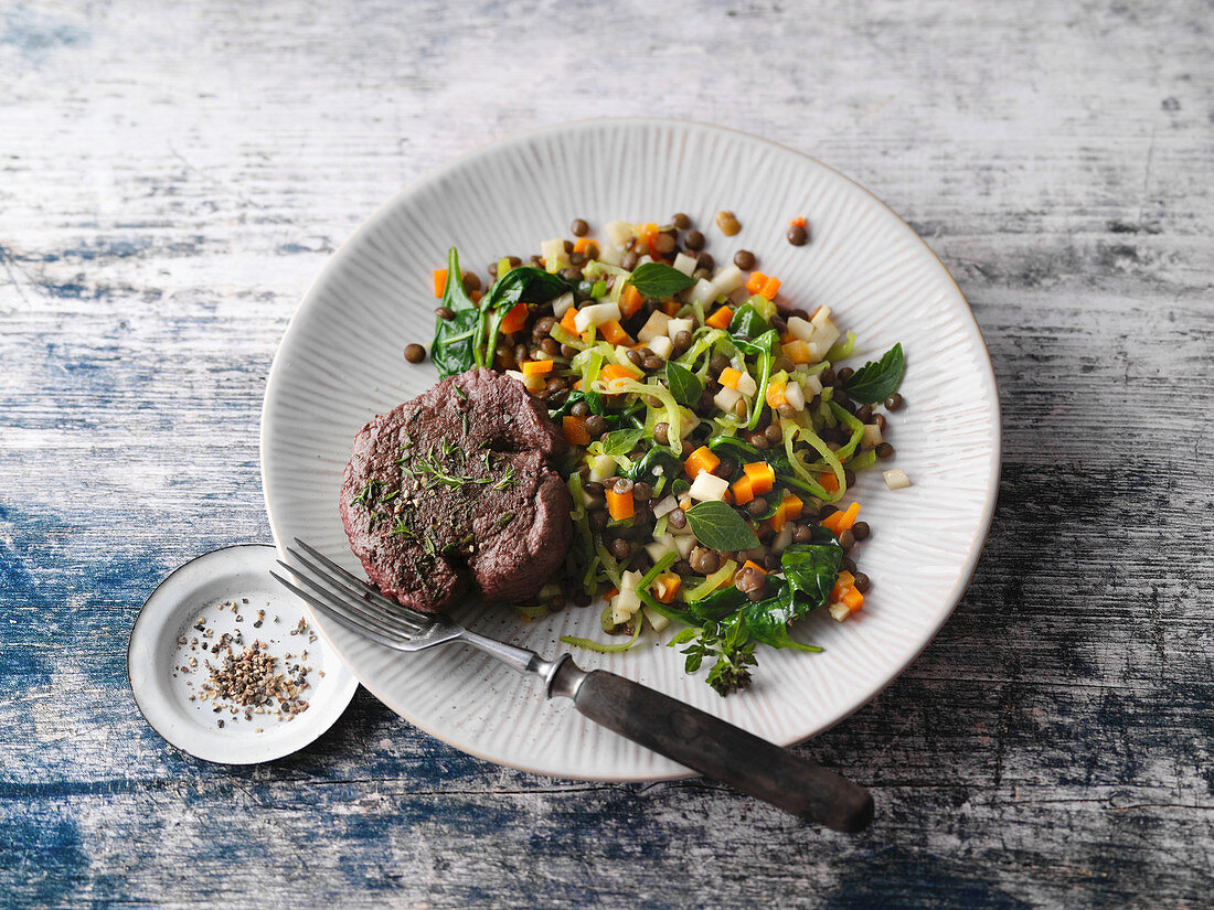 Roasted venison medallions on a bed of vegetables and lentils