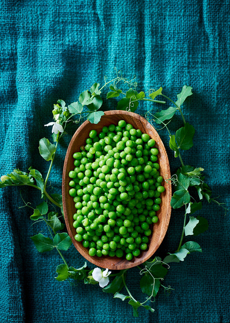 Peas in a wooden bowl with a leaf wreath