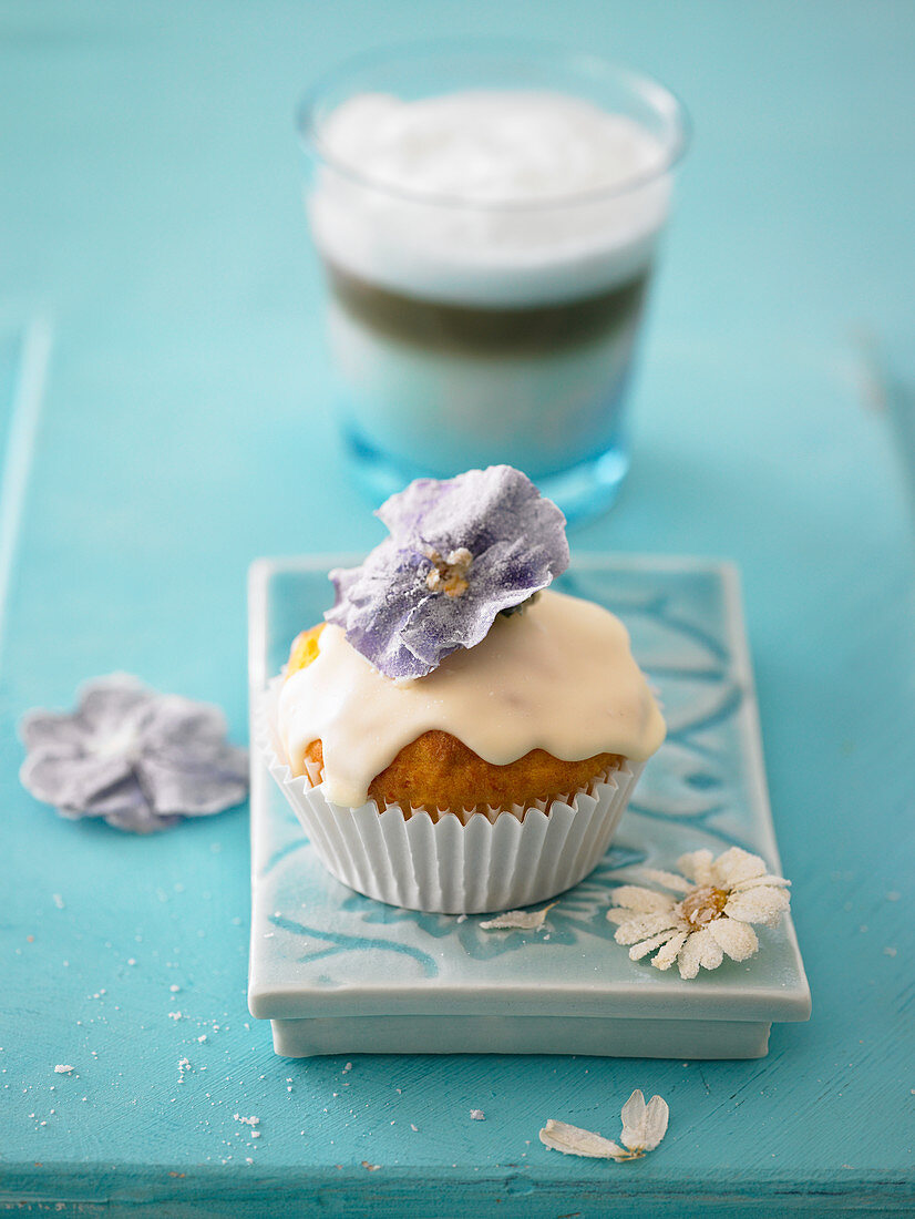 An eggnog muffin with icing and sugared flowers