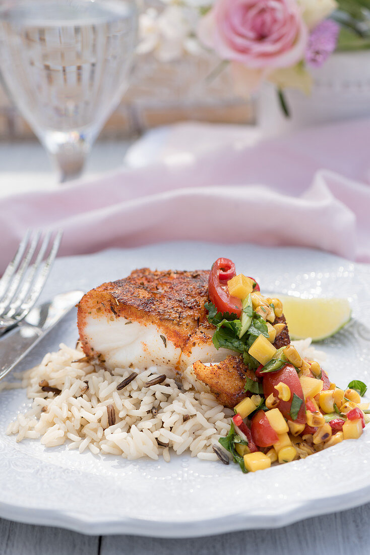 Breaded cod fillet with rice and salsa on a summer table outside