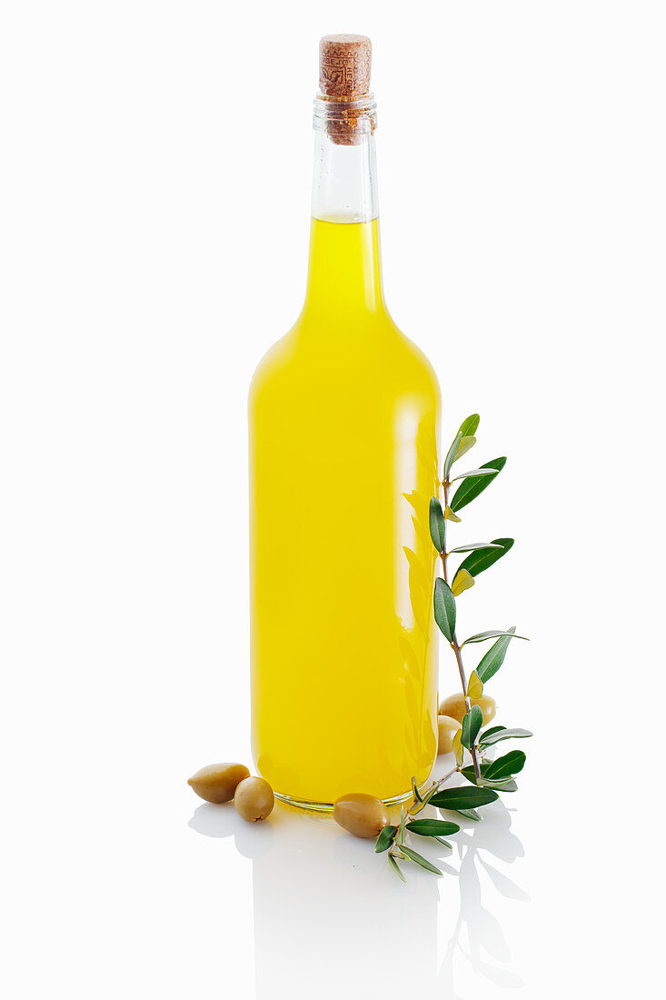 Olive oil in a glass bottle against a white background