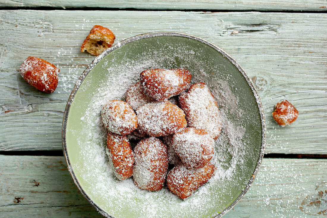A plate of homemade, deep-fried pastries with icing sugar (seen from above)