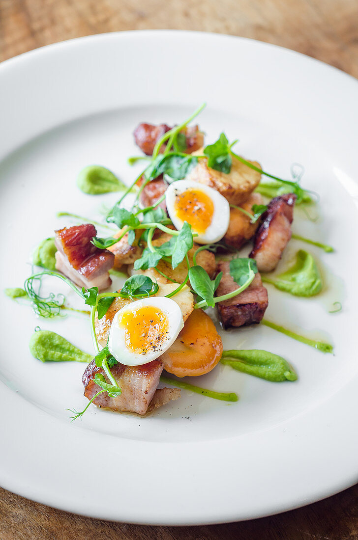 Pan fried bacon and scallops with quail eggs and a pea puree with pea shoots on a white plate and wooden table