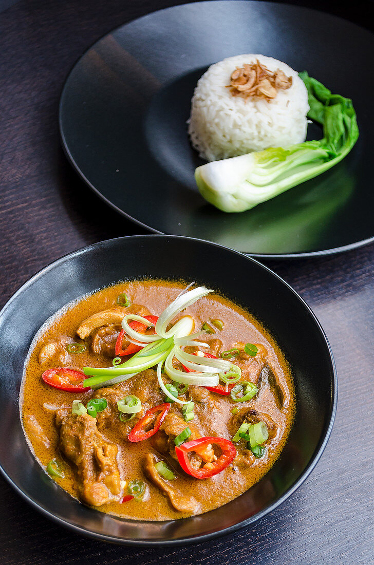 Thai red lamb curry with chilli, spring onions in a black bowl with rice and pack choi in the background