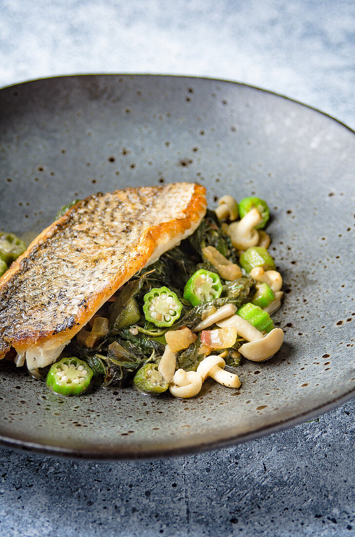 Pan fried trout fillet on a spinach, okra and wild mushroom sauteed in a dark bowl on a marble table