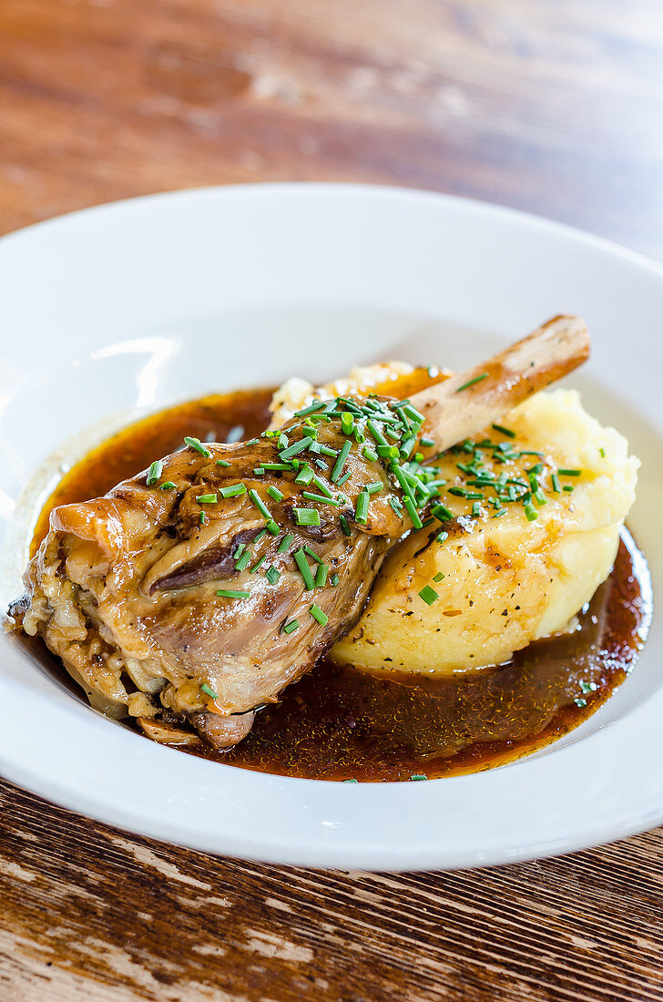 Plated lamb shank in a rich gravy on potato mash garnished with chives on a wooden background