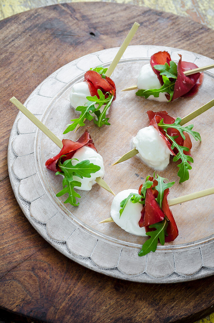 Buffalo mozzarella bites with bresaola and fresh rocket leaves canapes on a white wooden board and wooden background