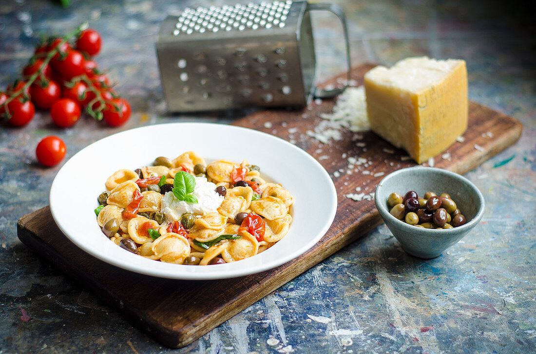 Fresh orecchiette pasta in a rich sauce with cherry tomatoes, green and kalamata olives, capers, fresh basil and ricotta cheese