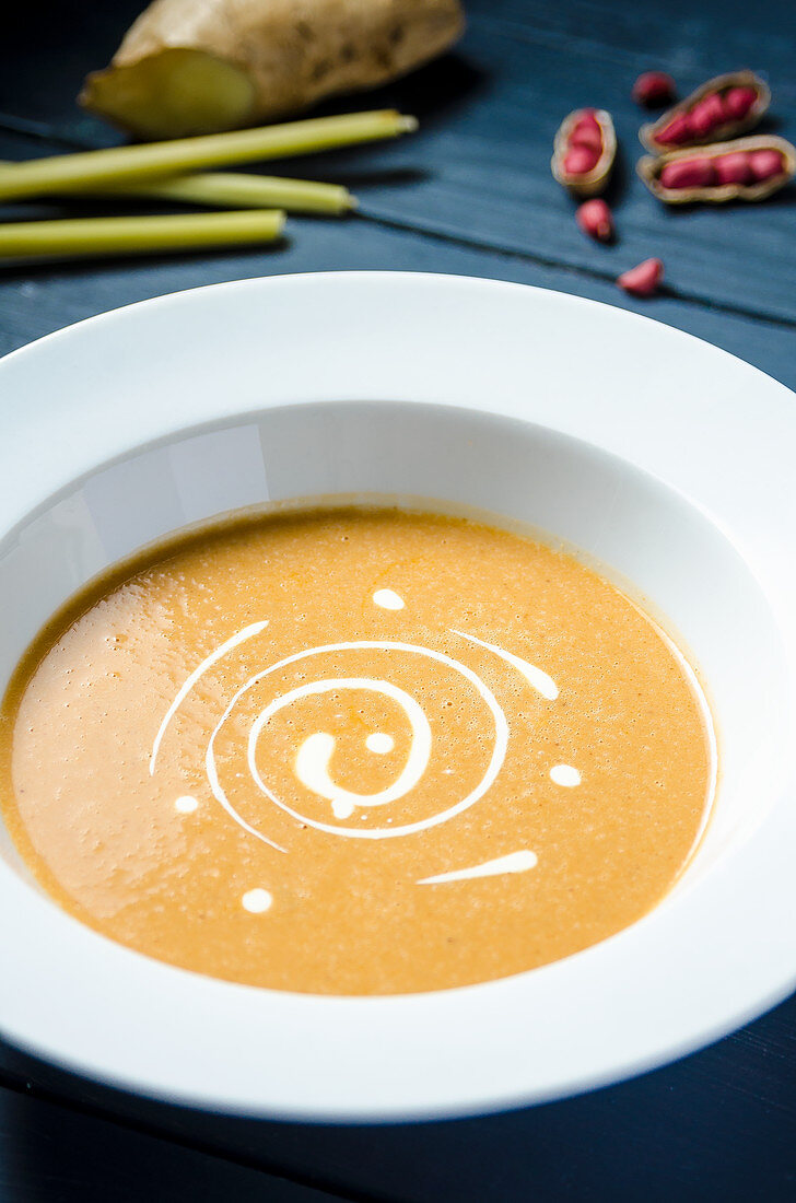 Sweet peanut cream soup garnished with double cream in a white plate