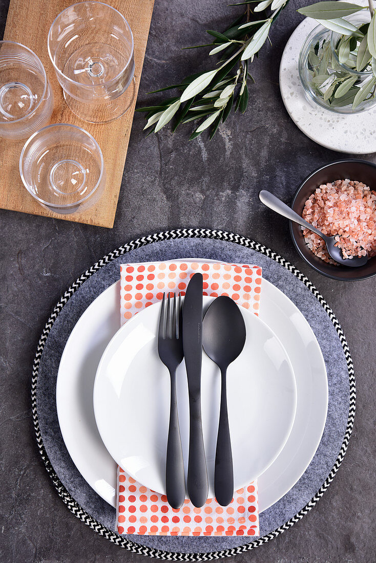 A place setting with a grey plate, white plates and black cutlery