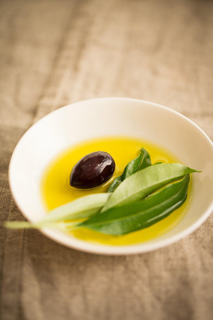 Olive oil with a black olive and an olive sprig in a bowl
