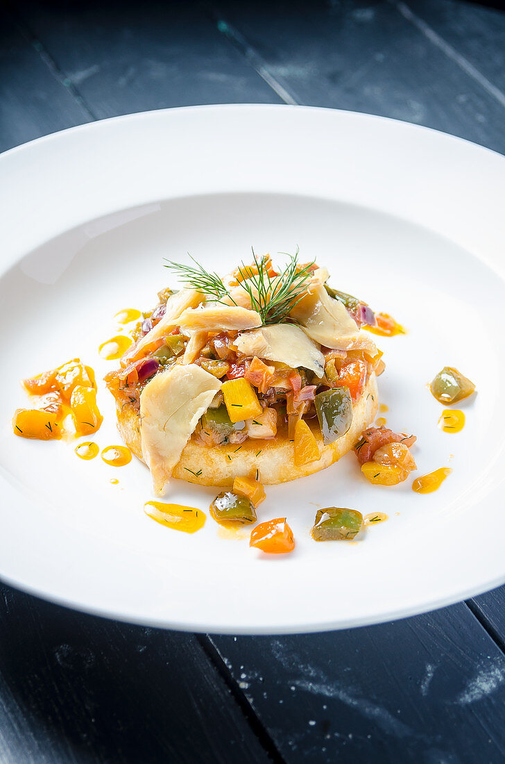 Spicy white fish cod fillet ina grenn, red and yellow pepper sauce on a swede mash garnished with dill in a white plate and blue table