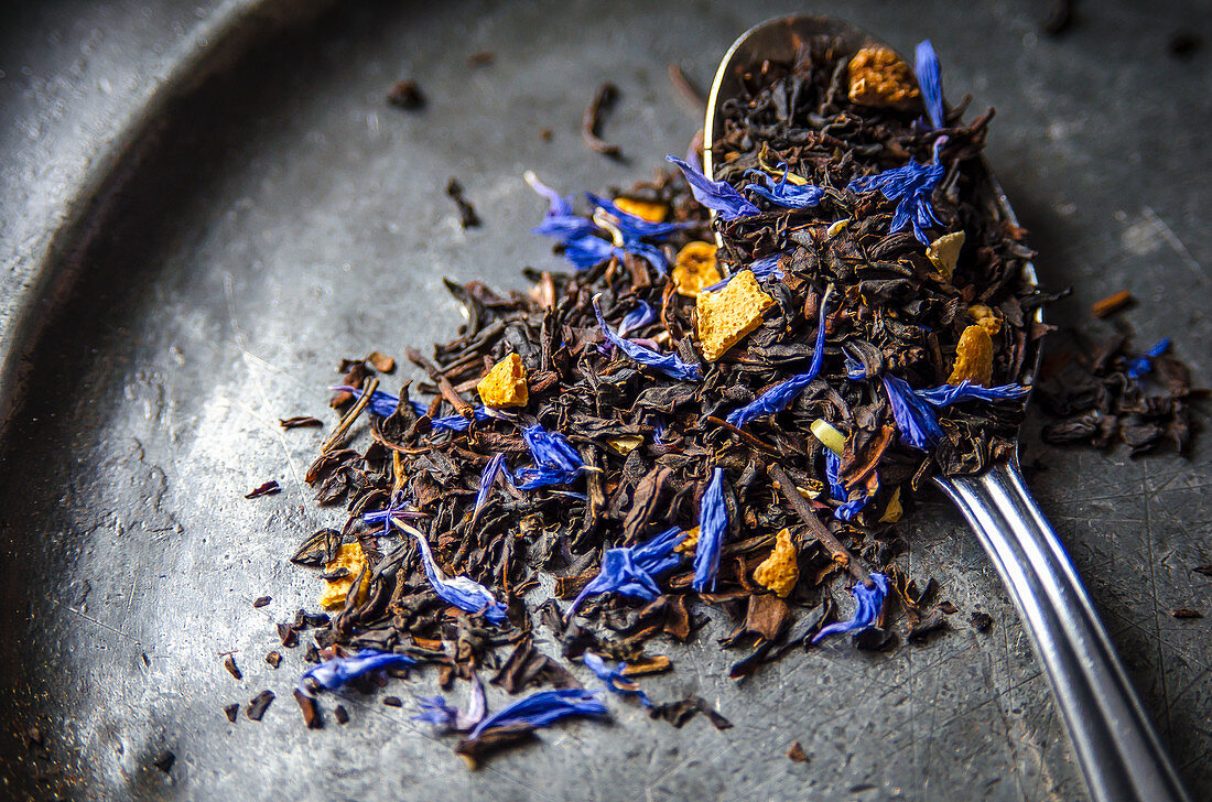 Loose leaf Earl Grey tea with dried citrus peel of lemon, orange and bergamot and blue cornflowers on a dark metal plate and a teaspoon