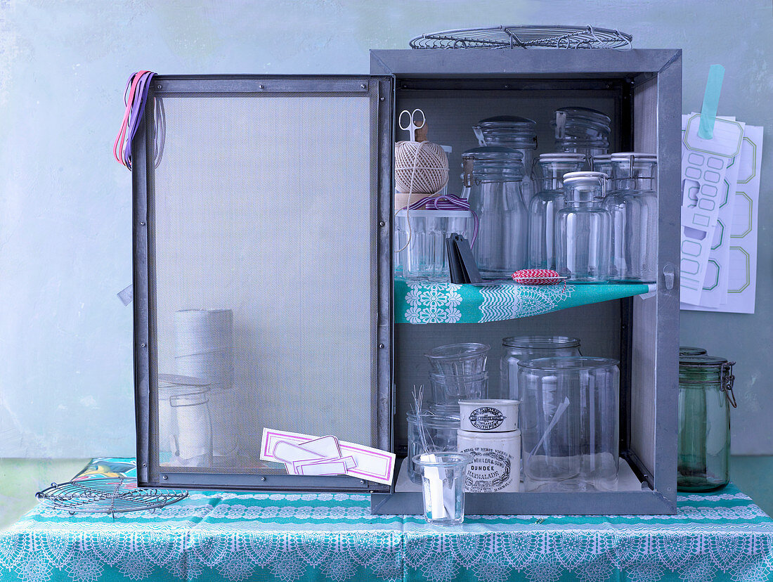 Empty preserving jars and utensils in the kitchen cupboard
