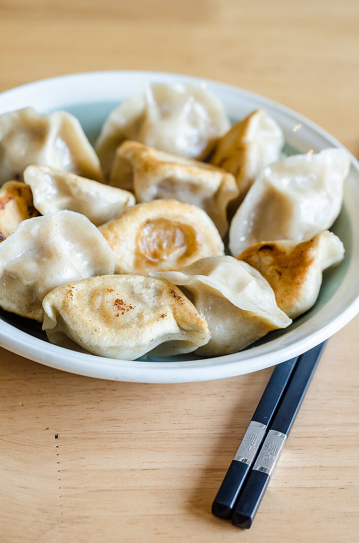 Bowl of grilled dchinese dumplings with chopsticks on a wooden table