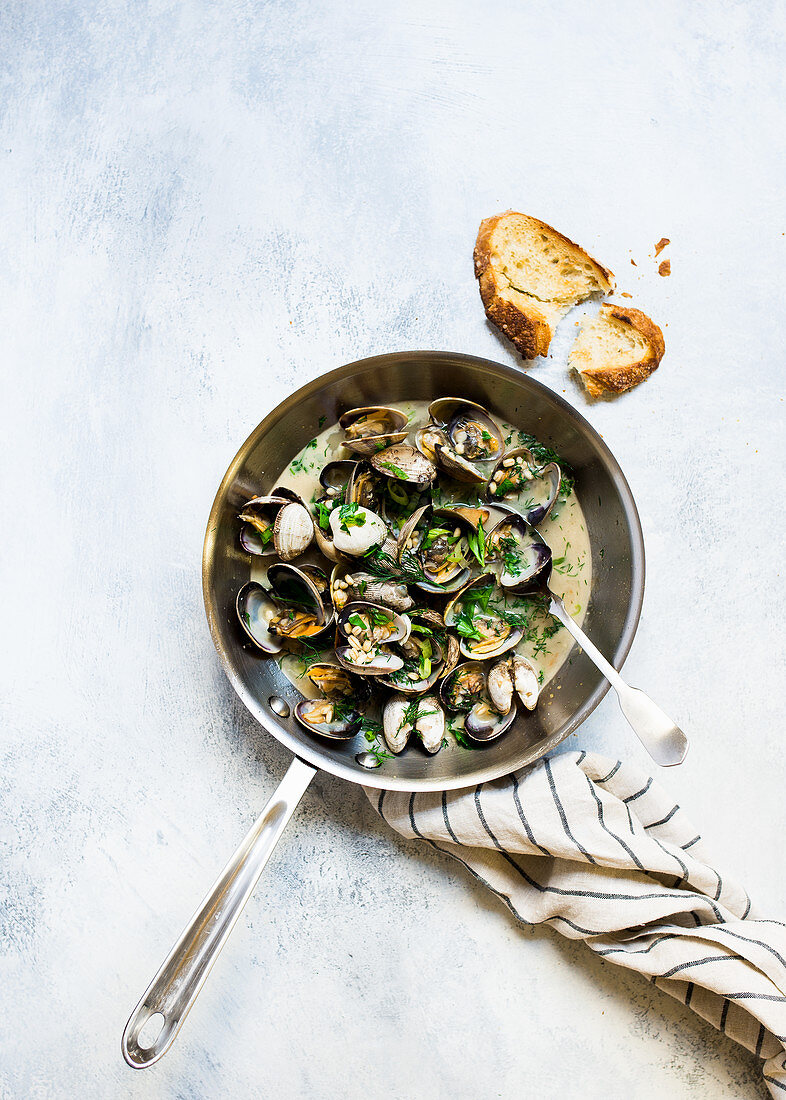 Mussels in garlic and white wine sauce served in a pan with bread