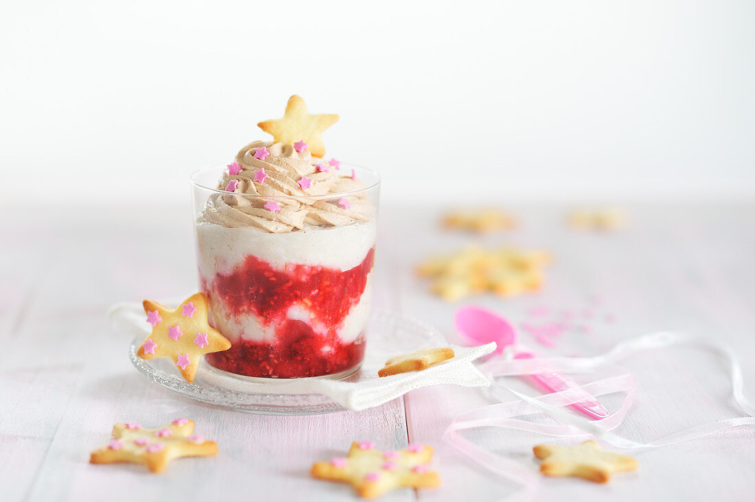 Coconut and almond cream in a jar with raspberry compote, chocolate cream and baked vanilla stars (vegan)