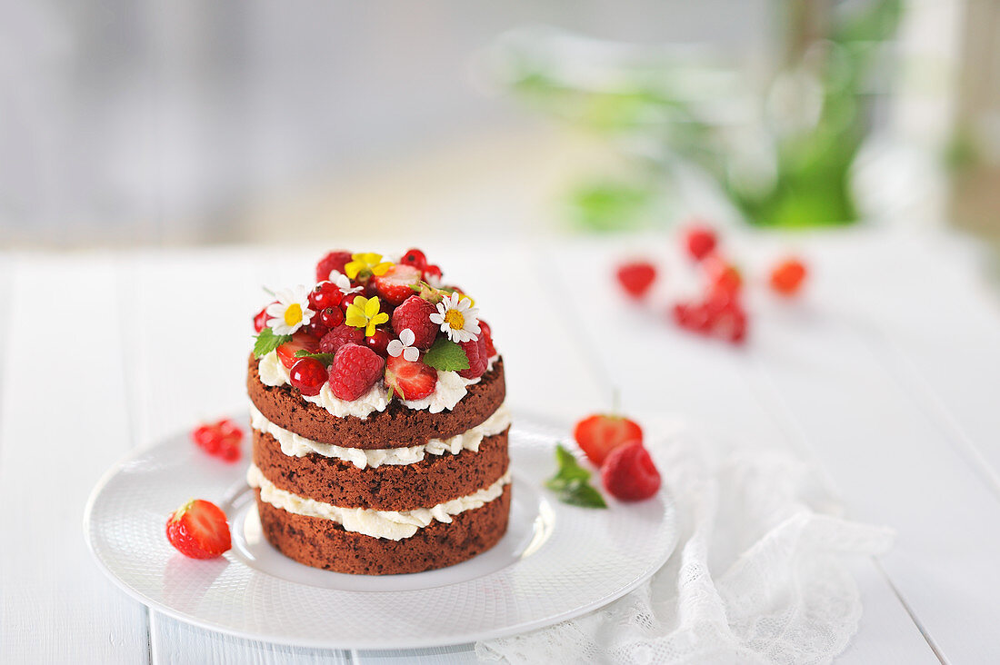 A mini naked cake with chocolate sponge, white chocolate cream, fresh berries and flowers (vegan)
