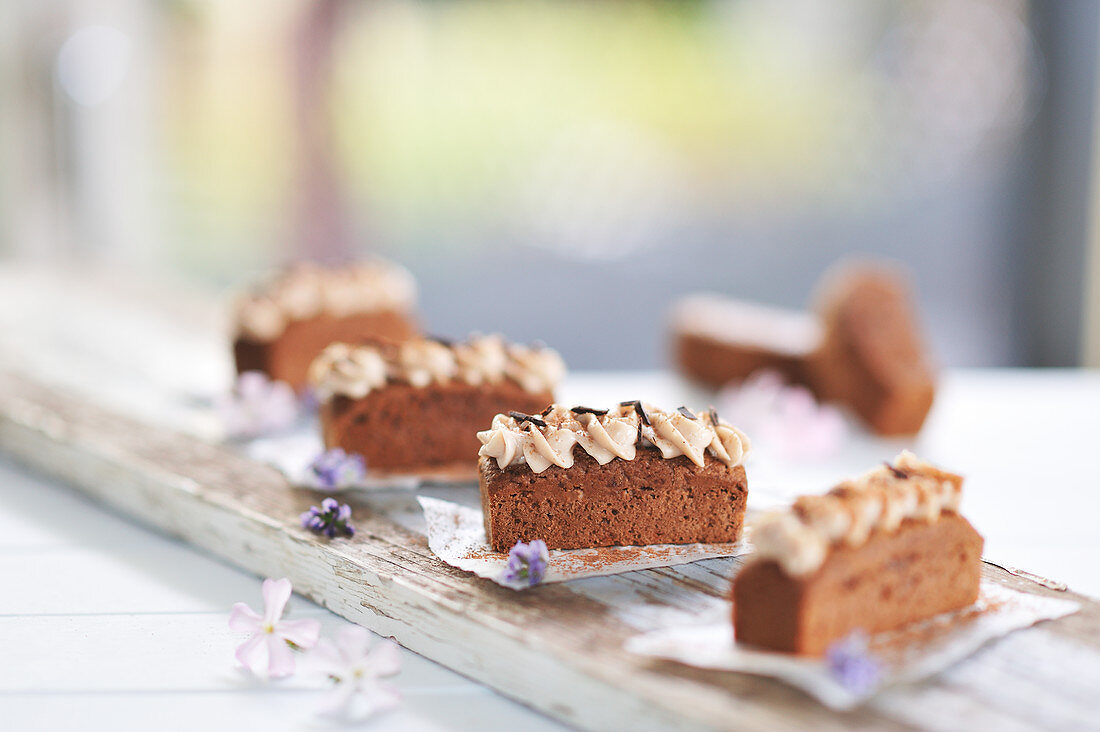 Mocha chocolate cake slices with almond cream and chocolate chips on a wooden board (vegan)