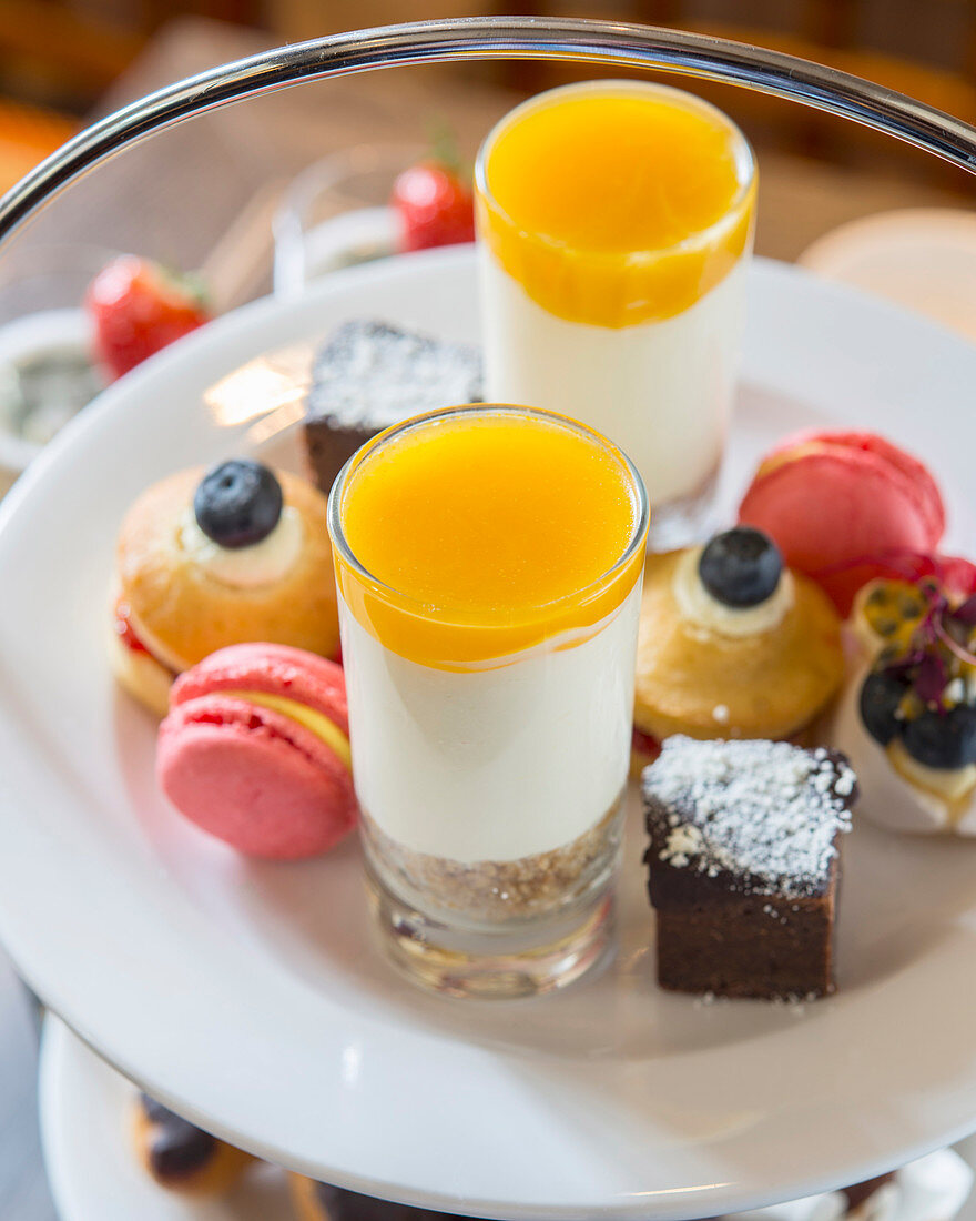 Petit fours, macaroons and layered desserts for tea time on a cake stand