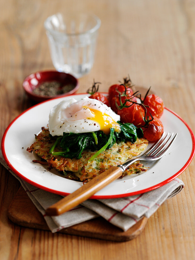 A rösti topped with a fried egg, spinach and grilled vine tomatoes