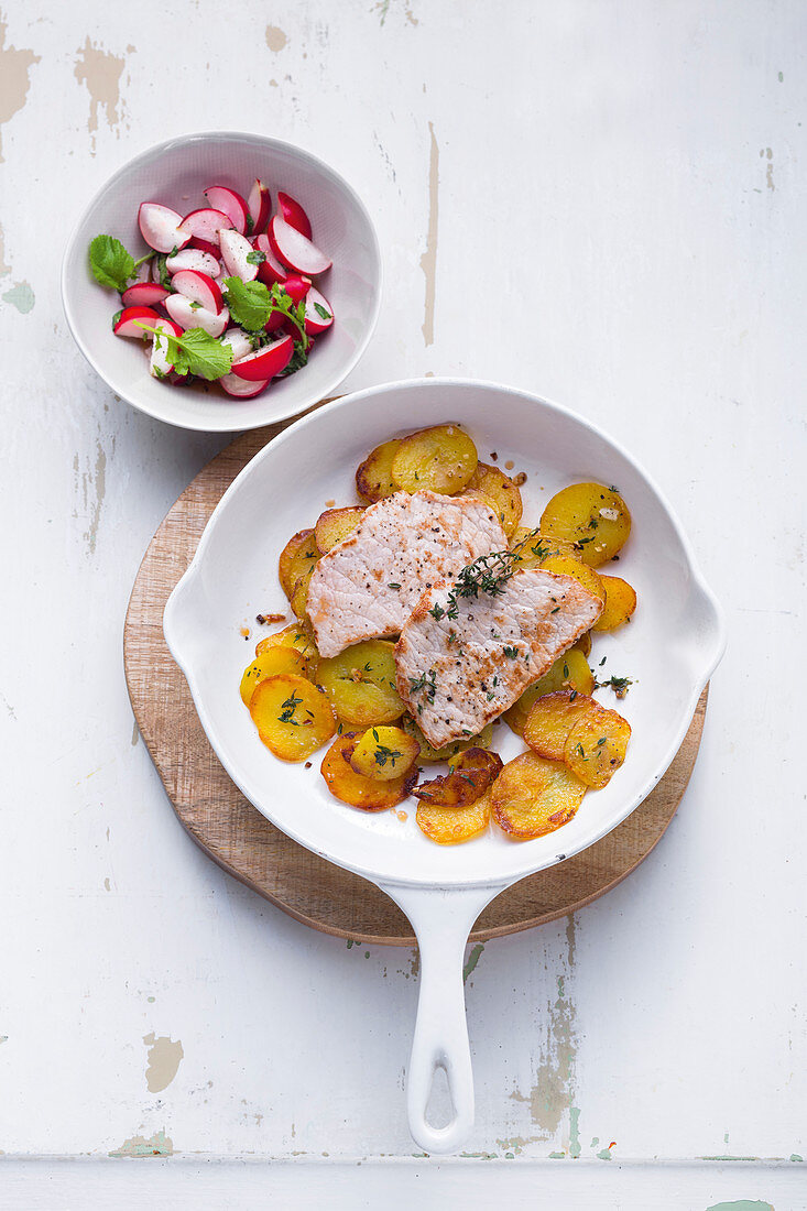 Minute schnitzel with fried potatoes and a radish salad