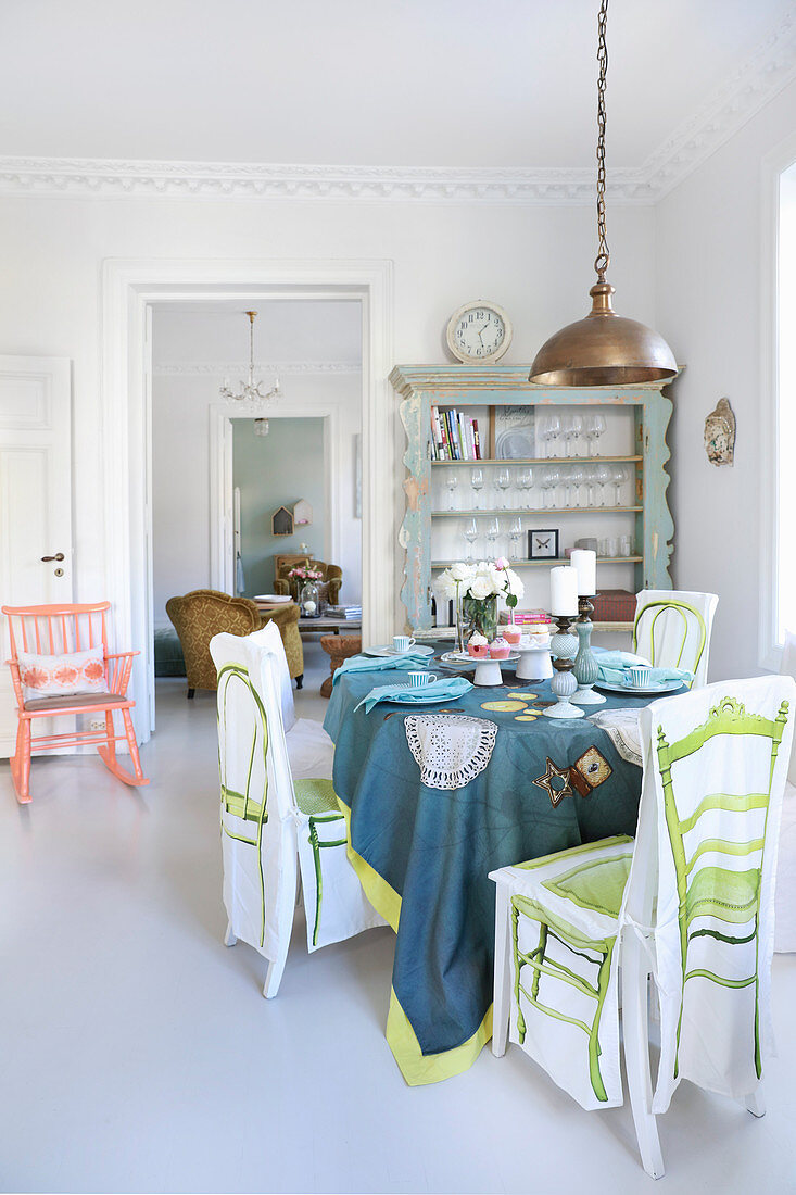 Set table in white dining room with brightly coloured accents