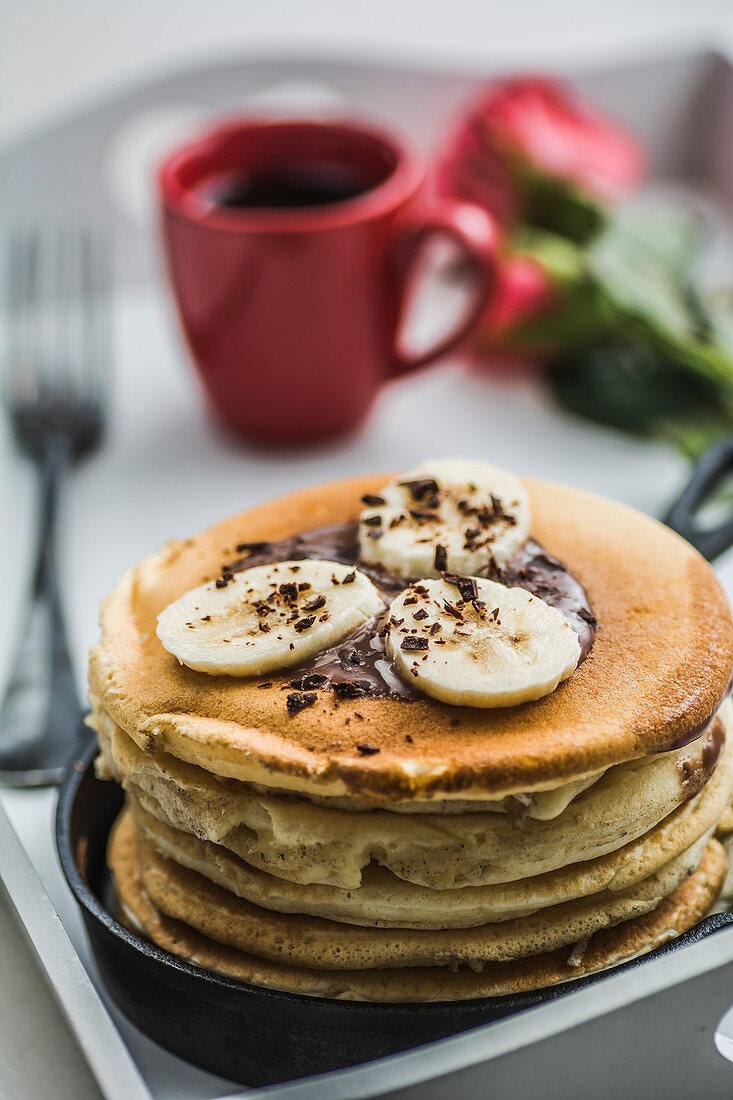 Ein Stapel Pancakes mit Bananen und Schokolade