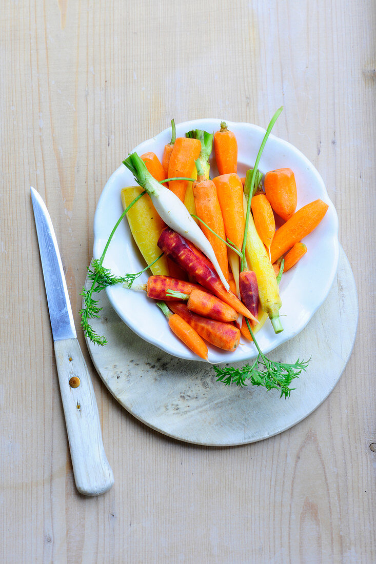 Various brightly coloured peeled carrots on a plate (top view)