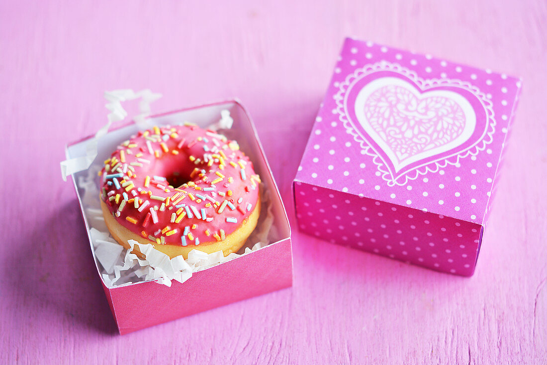 Mini doughnuts with icing and sugar sprinkles in a gift box