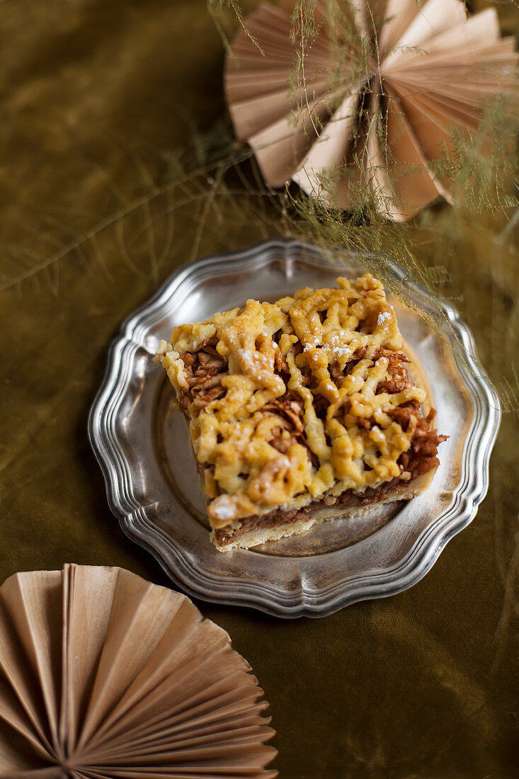 A slice of apple cake with streusel on a pewter plate