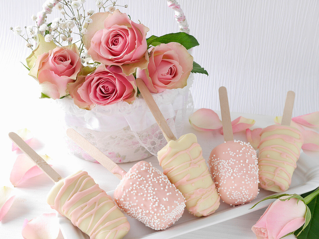 Cheesecakes on sticks with white and pink chocolate icing