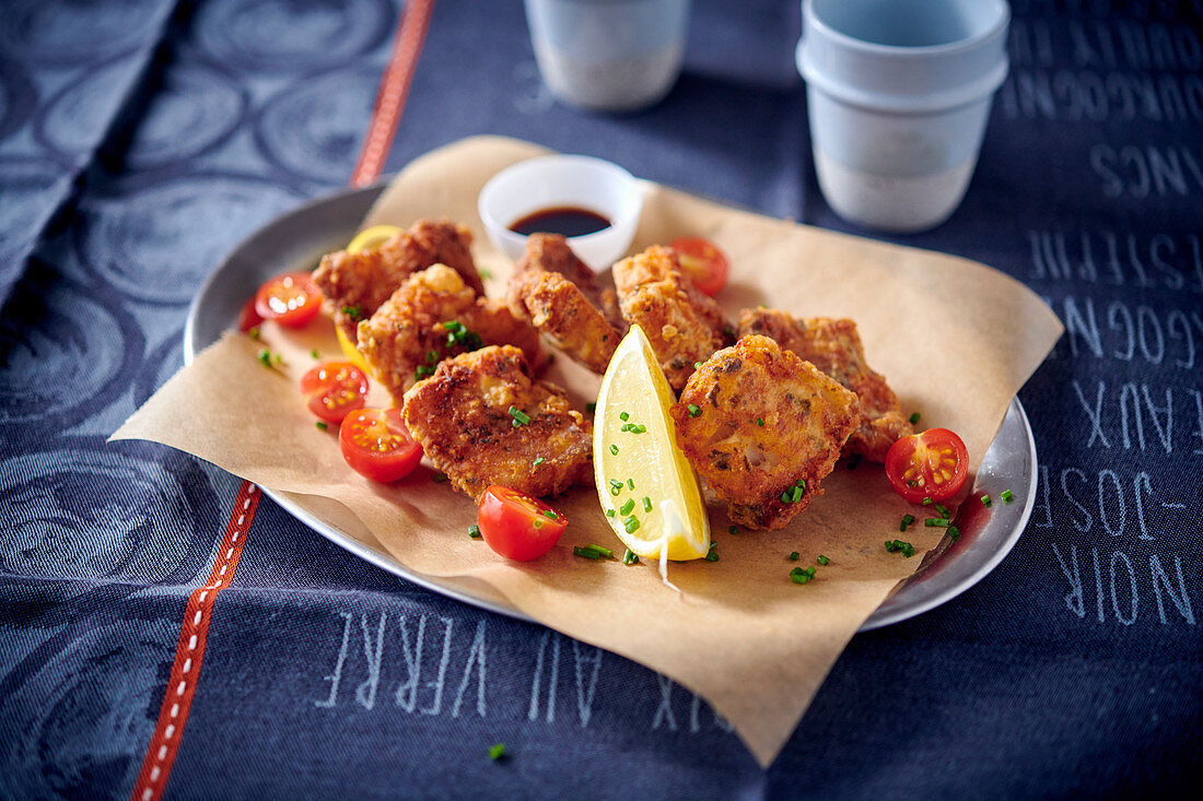 Breaded, fried hake with cherry tomatoes on baking paper