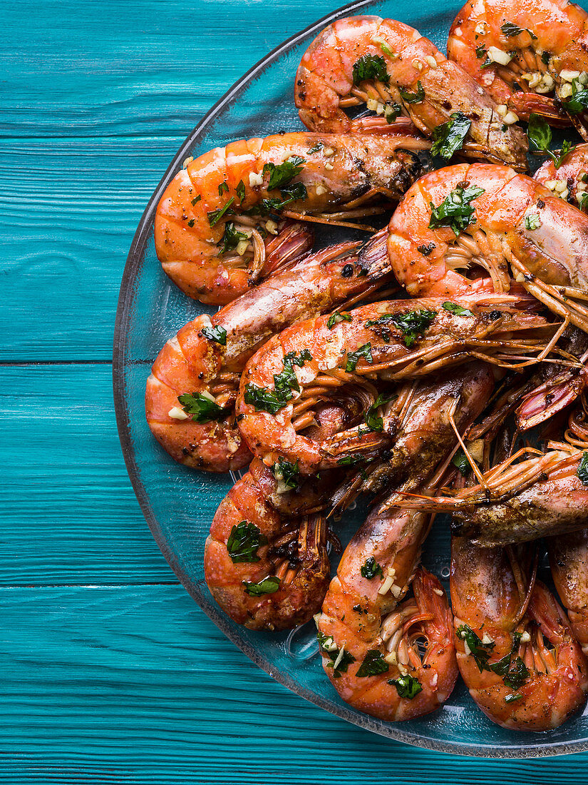 Grilled shrimps served on a dish with olive oil, parsley and garlic over dark green wooden background