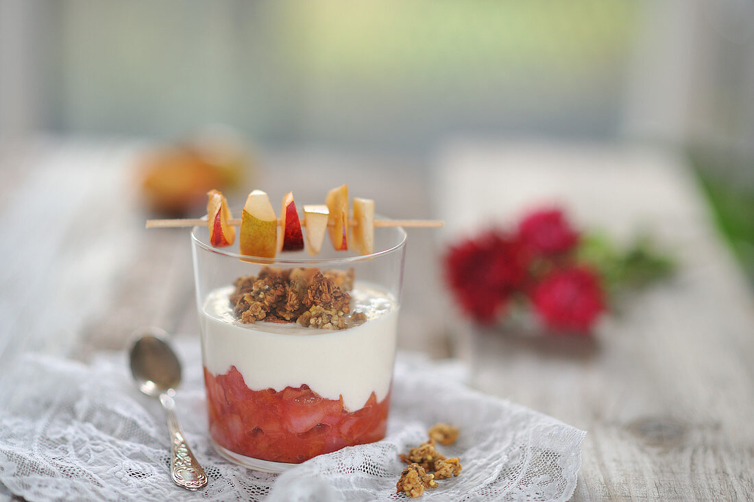 Plum and pear compote in a glass with coconut yoghurt, granola and a fruit skewer (vegan)