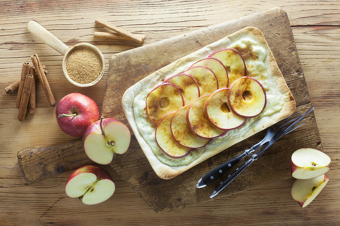 Tarte flambée with apples, sugar and cinnamon on a wooden surface
