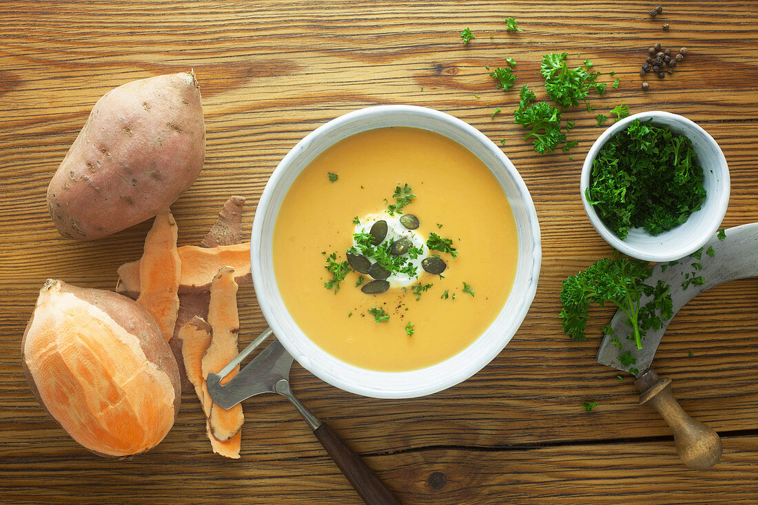 Sweet potato soup with ingredients on a wooden surface