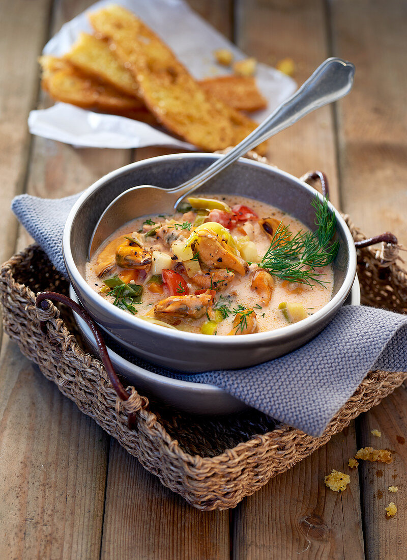 Seafood soup in a soup terrine with a spoon on a cork tray