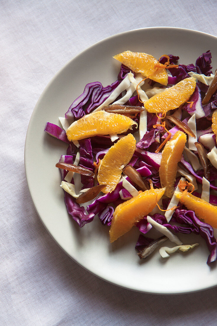 A raw and healthy winter salad ith red cabbage, white cabbage, dates, orange, zest of orange