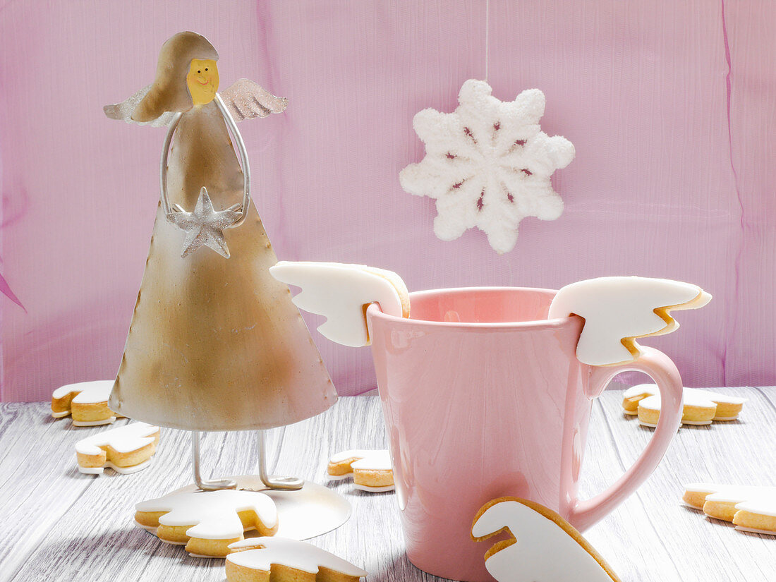 A cup with angel wing cup biscuits and an angel figure