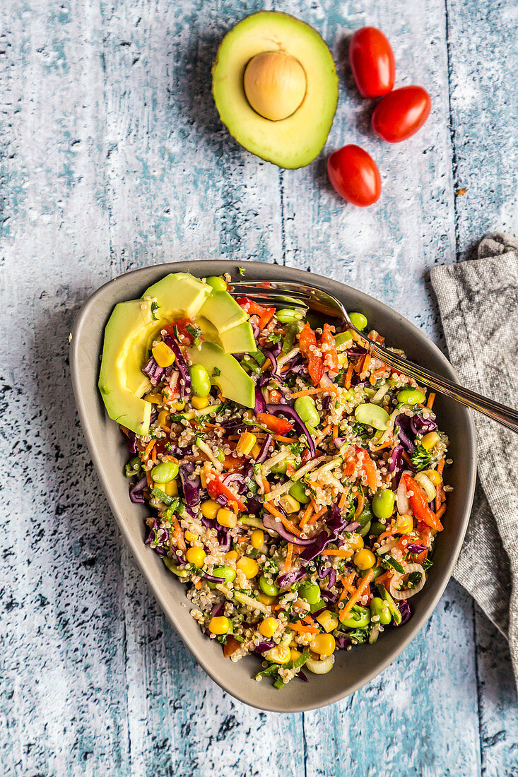 Colourful quinoa salad with edamame, sweetcorn, carrots, tomatoes, peppers and onions