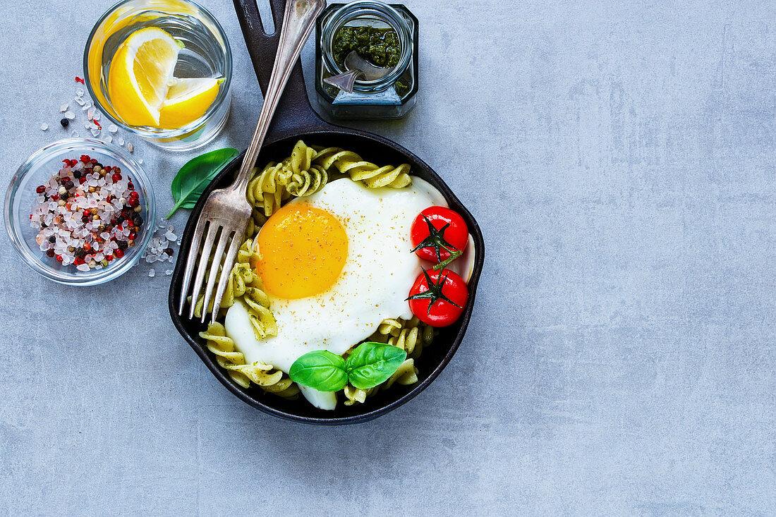 Nudelpfanne mit Pesto, Spiegelei, gebratenen Tomaten und Basilikum
