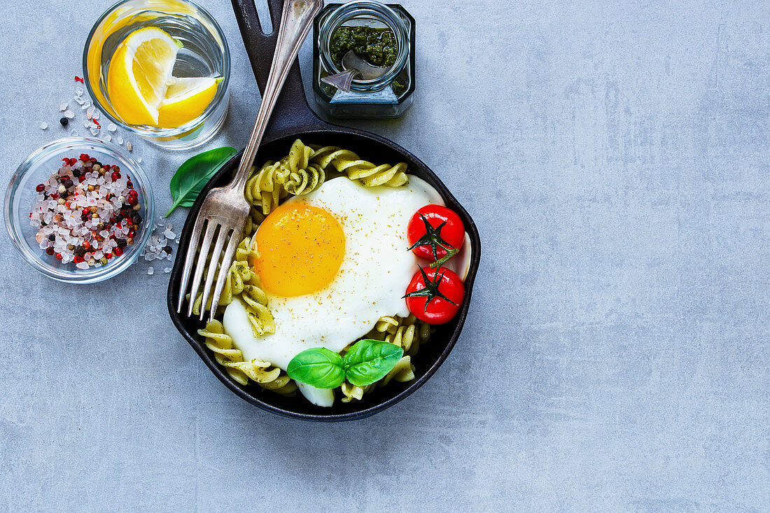 Old frying pan of tasty italian pasta with pesto sauce, fried egg, roasted tomatoes and basil