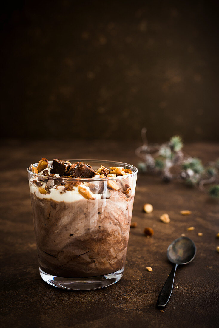 Chocolate pudding with roasted nuts and cream in a glass