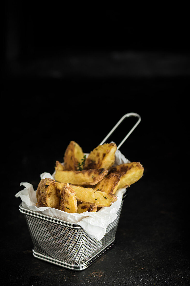 Potato wedges with thyme and Parmesan cheese in a frying basket